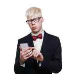 Albino young man in suit with mobile isolated.