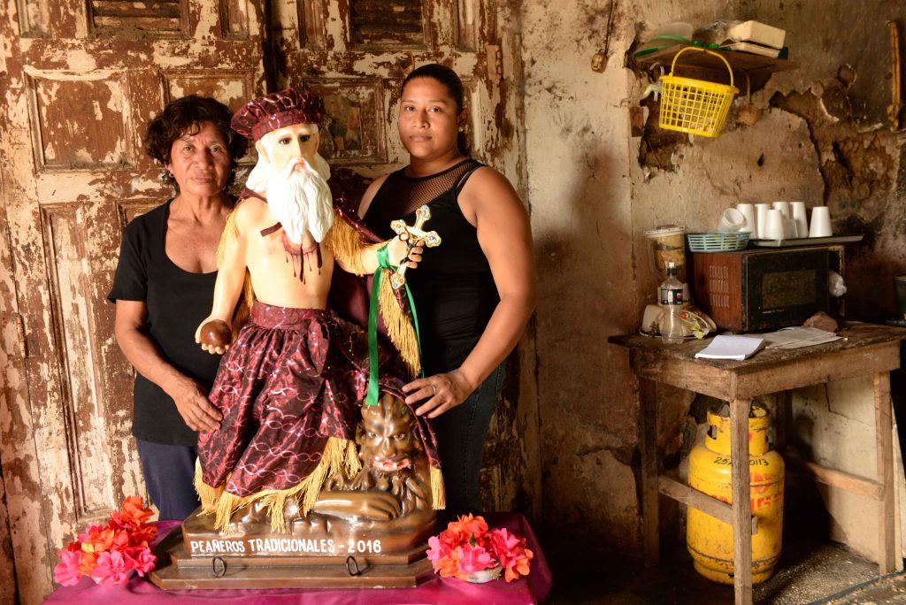 """Doña Gloria Flores, de 65 años, madre de Javier Gaitán, y Raity Flores, de 29, su viuda. Esta es la réplica de San Jerónimo que Javier dio a elaborar y que nunca pudo ver. La imagen lo acompañó durante la vela y luego al cementerio, """"bailando"""" por las calles de Masaya."""