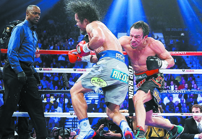 Juan Manuel Marquez, from Mexico, right, connects against Manny Pacquiao, from the Philippines, as referee Kenny Bayless looks on at left, during their WBO world welterweight fight Saturday, Dec. 8, 2012, in Las Vegas. Marquez won the fight by a knockout. (AP Photo/Julie Jacobson)