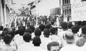 FOTO TOMADA POCO ANTES DE QUE SE INICIARA LA MASACRE DEL 22 DE ENERO DE 1967 en las esquinas de los entonces bancos Central y Nacional. A la derecha, como es en la actualidad, sede de la Asamblea Nacional. Quedan algunos de los árboles de laurel de la india desde donde cayeron muertos muchos manifestantes. El primer muerto fue el teniente Sixto Pineda.
