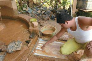 Léster Monge muestra los residuos que expulsa el molino. El oro más pesado se acumula bajo el agua.