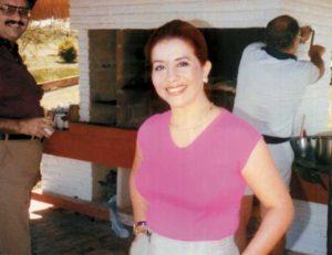 Dinorah sonríe , en una foto de su álbum familiar. En el fondo se aprecia a Somoza, mientras prepara un asado en el Paraguay.
