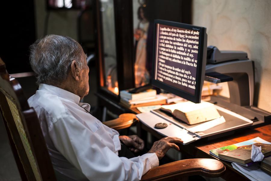 Entre sus descansos lee, auxiliado por la máquina que proyecta en imagen aumentada las letras. Le gusta la literatura latinoamericana, pero ahora solo lee la Biblia y texto religiosos. Foto Oscar Navarrete.