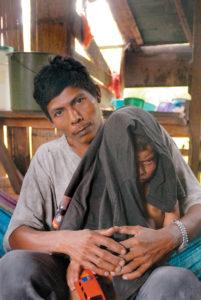 Solano Paterson y su hijo Marlon, a quien cubre para que no le dé el sol.