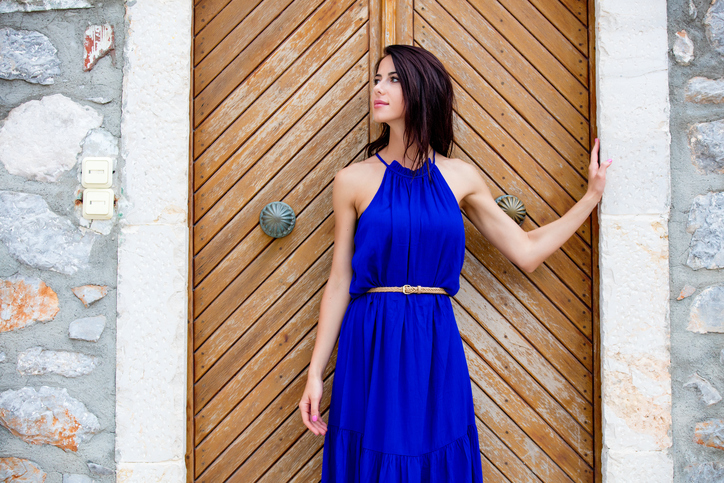 photo of beautiful young woman standing near the wooden old door in Greece