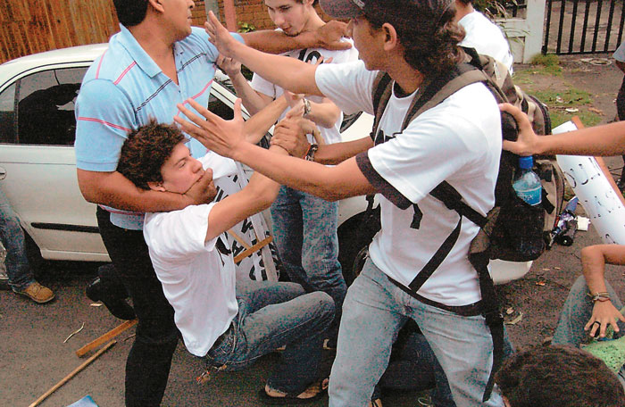 Bernardo Herrera, de perfil a la derecha, reclama por la paliza que grupos de choque gubernamentales le dieron a jóvenes frente a las instalaciones de Canal 4