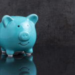 Blue shiny piggy bank on dark reflection black floor with loaft cement wall background with copy space