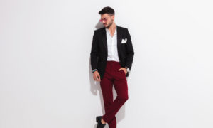relaxed elegant man leaning against wall looks down to side