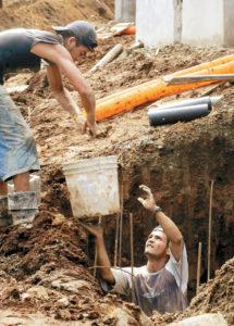 Dos obreros nicaragüenses en plena faena en Playa Los Cocos.