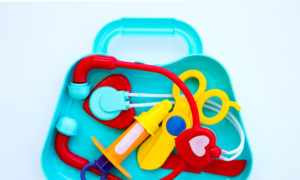 Kid's toy doctor set in blue plastic bag on white backround