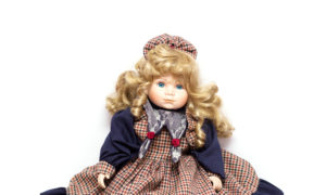 Old porcelain doll on White Background. Concept of time.