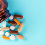 Heap of colorful medical pills and tablets spilling out of a drug bottle on blue background. Top down view with copy space.