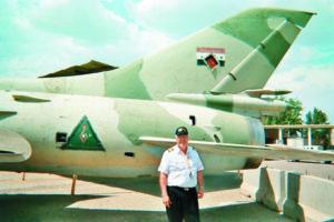 El piloto Roberto Amador posa en Bagdad a la par de un antiguo MIG 21 que perteneció a la fuerza aérea iraquí de Saddam Hussein.